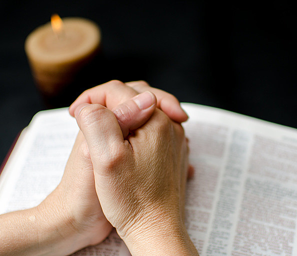 Hands of a woman clasped over Bible, daily Christian